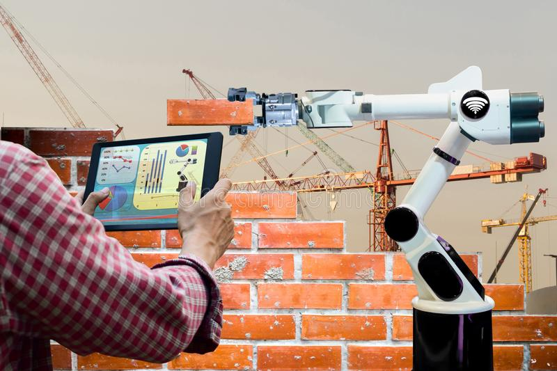 Укомплектуйте личным составом держать индустрию 4 робота дистанционного управления таблетки умную 0 конструкций кирпичного здания стоковые изображения rf