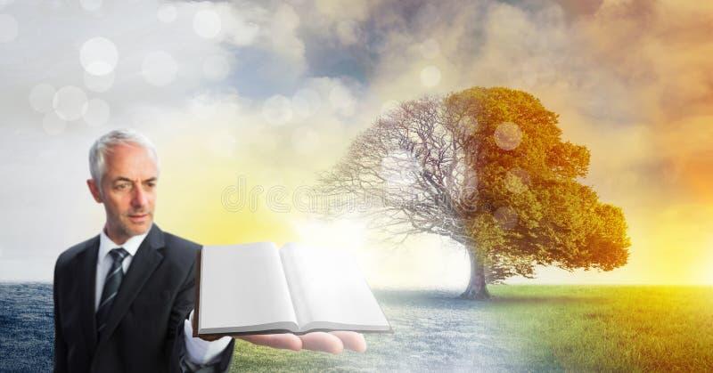 Укомплектуйте личным составом держать книгу с волшебным сюрреалистическим сезонным воображением дерева стоковые фото