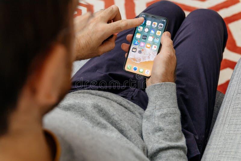 Укомплектуйте личным составом держать новое iPhone x 10 Displa Яблока стоковые фотографии rf