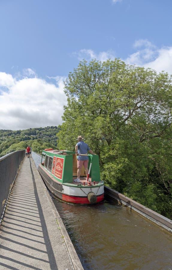 Укомплектуйте личным составом держать румпель мост-водовода скрещивания narrowboat Великобритания стоковая фотография