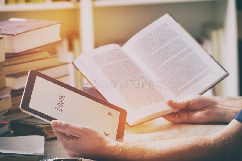 Укомплектуйте личным составом держать современных читателя и книги ebook в библиотеке стоковое изображение rf