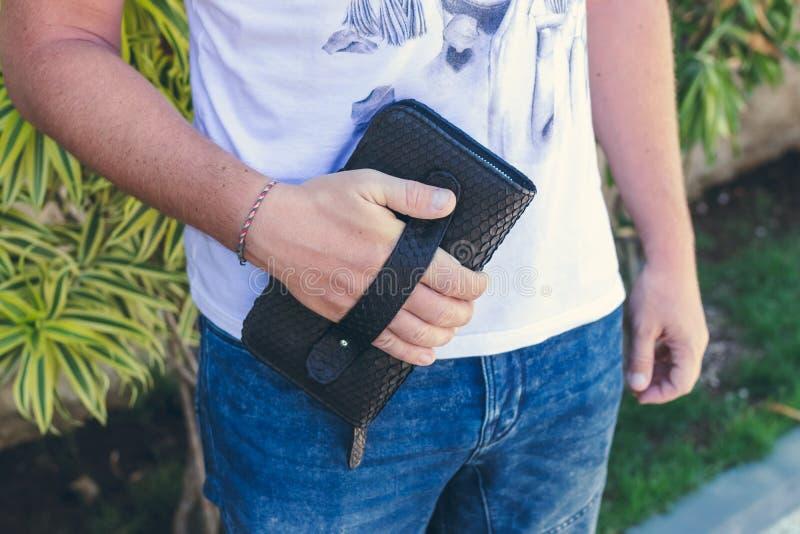 Укомплектуйте личным составом держать handmade портмоне сделанный от экзотического кожаного питона snakeskin, outdoors, предпосыл стоковое фото