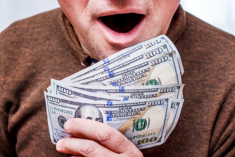 Укомплектуйте личным составом держит деньги в его руке и раскрыл его рот в сюрпризе, u стоковое фото rf