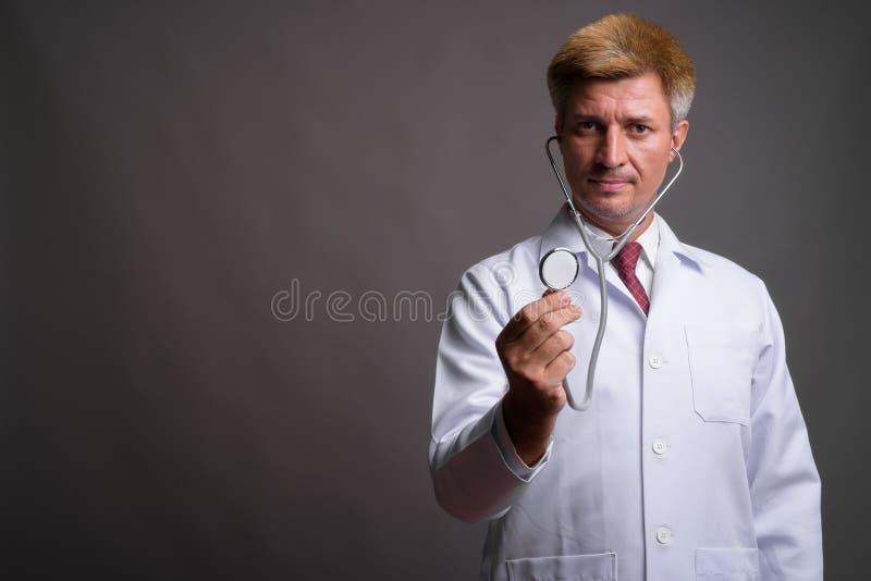 Укомплектуйте личным составом доктора с светлыми волосами используя стетоскоп против серого backgr стоковое фото rf