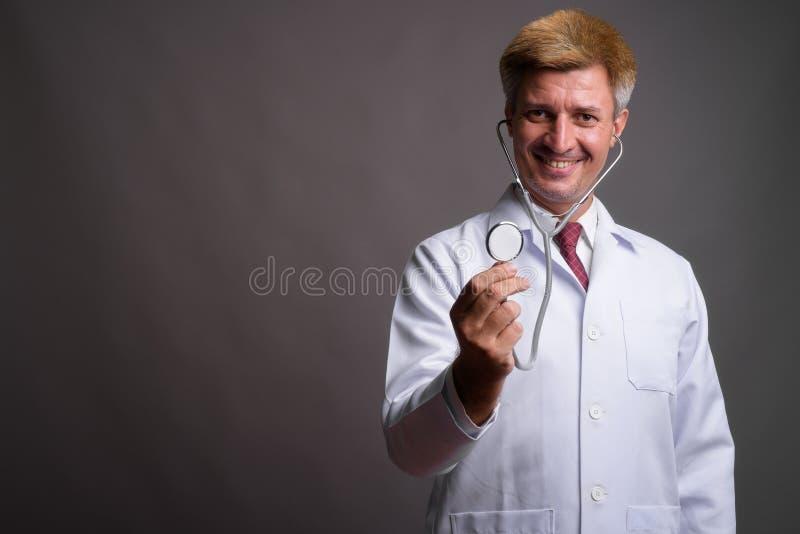 Укомплектуйте личным составом доктора с светлыми волосами используя стетоскоп против серого backgr стоковое фото