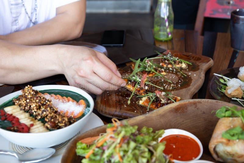 Укомплектуйте личным составом еду всей пиццы зерна с овощами и здоровой едой на деревянной доске стоковые изображения