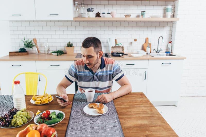 Укомплектуйте личным составом есть завтрак используя умный телефон в кухне дома стоковое фото rf