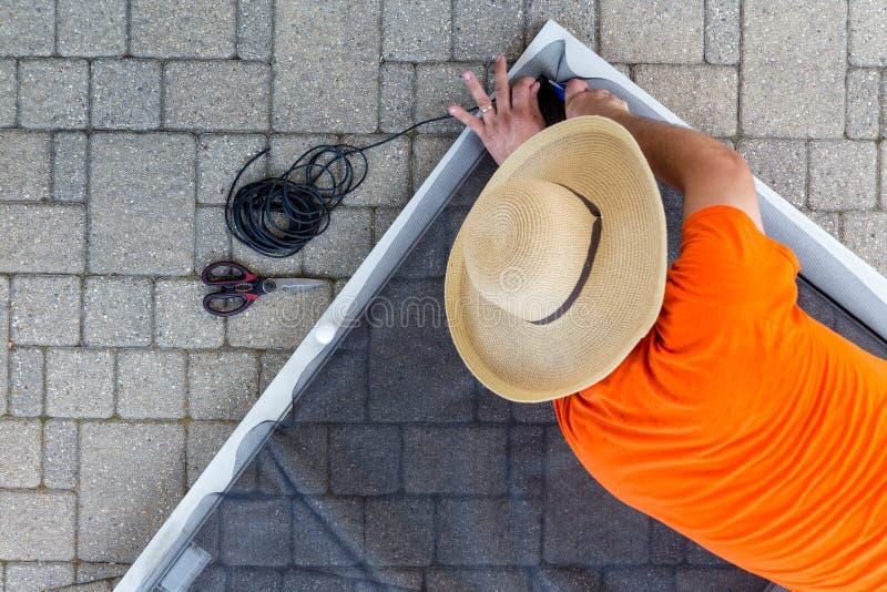 Укомплектуйте личным составом заменять поврежденную ячеистую сеть на двери с защитной сеткой стоковые фото