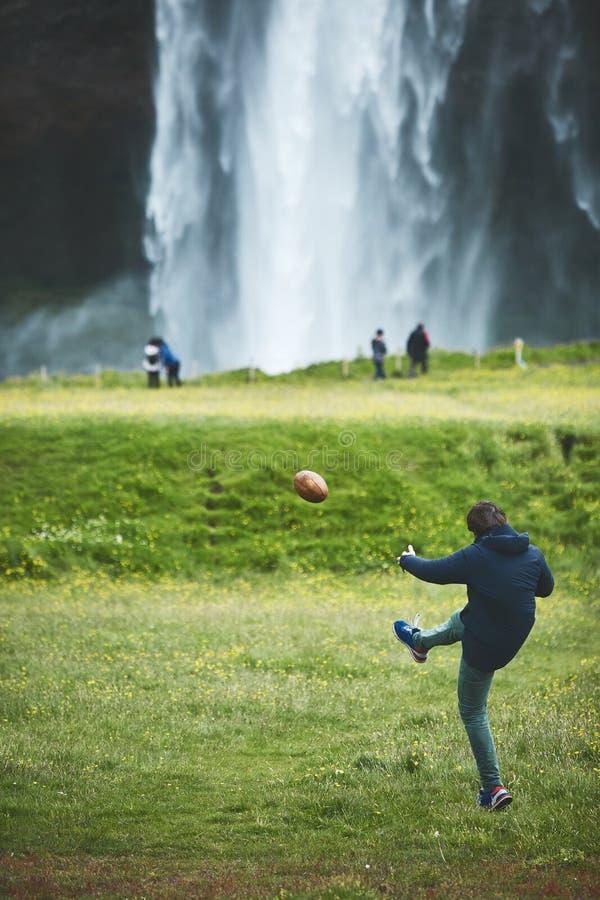 Укомплектуйте личным составом играть шарик около известного водопада Seljalandsfoss в южной Исландии стоковое фото rf