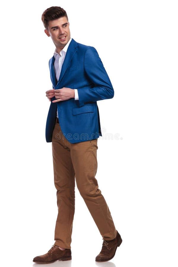 Укомплектуйте личным составом идти, застегивать его пальто и рассматривать его плечо стоковая фотография rf