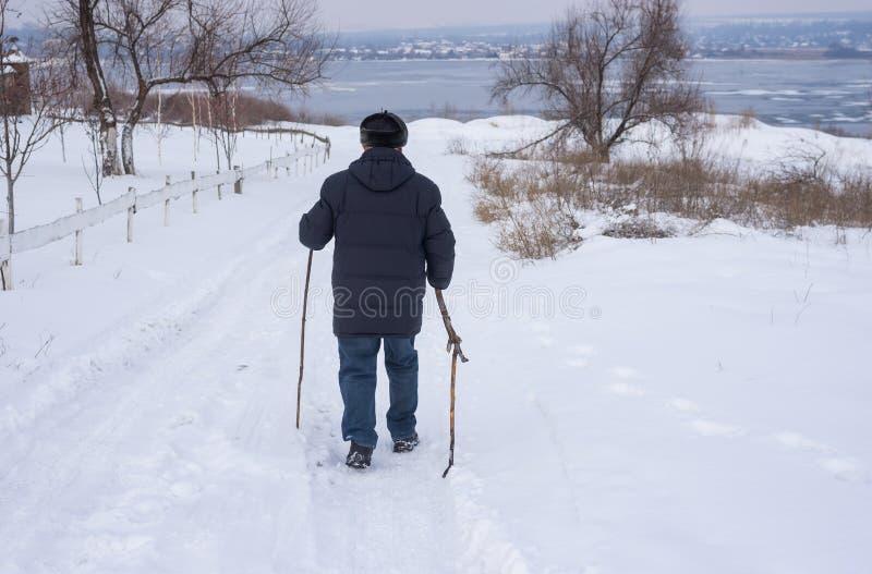 Укомплектуйте личным составом идти на снежную дорогу вниз к замороженному реке Dnipro в Украине стоковые фотографии rf