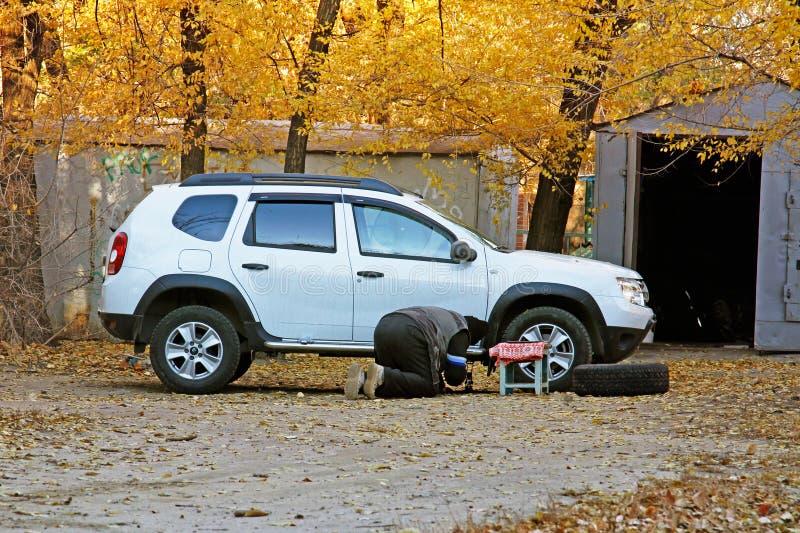 Укомплектуйте личным составом изменяя покрышку на автомобиле около гаража в дворе в Волгограде стоковое фото rf