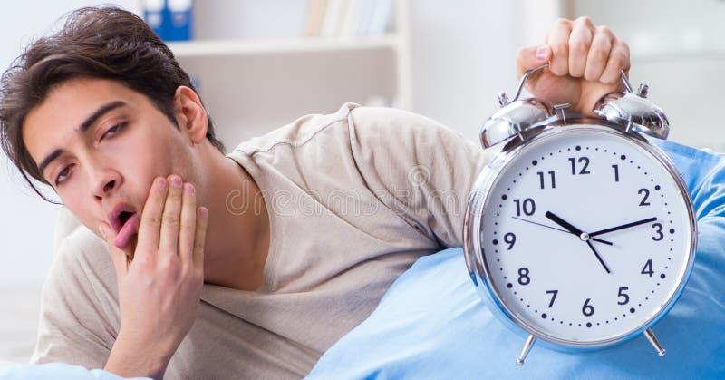 Укомплектуйте личным составом иметь тревогу просыпая вверх с будильником стоковая фотография