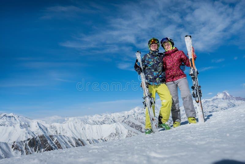 Укомплектуйте личным составом и девушка стоя на наклоне с горными лыжами Зима hu стоковое изображение