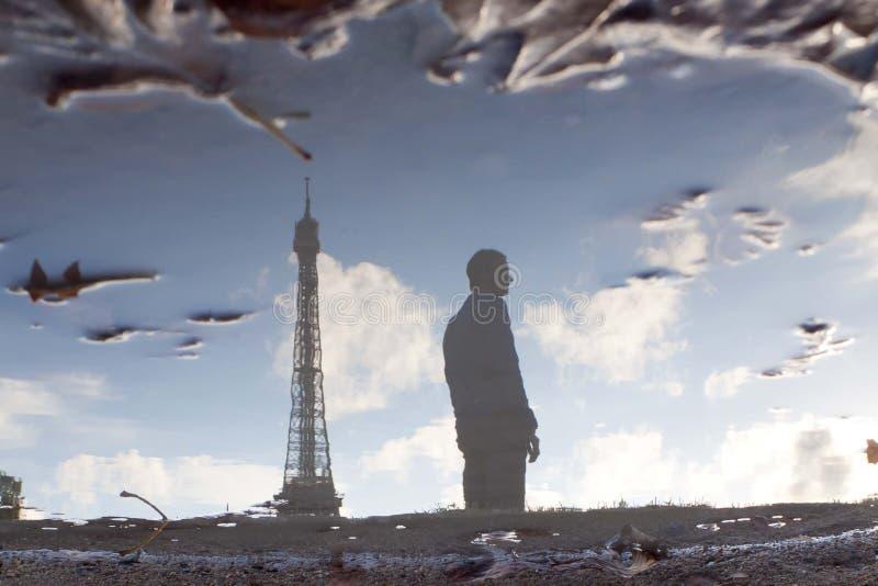 Укомплектуйте личным составом и Эйфелева башня отраженная в лужице стоковая фотография rf