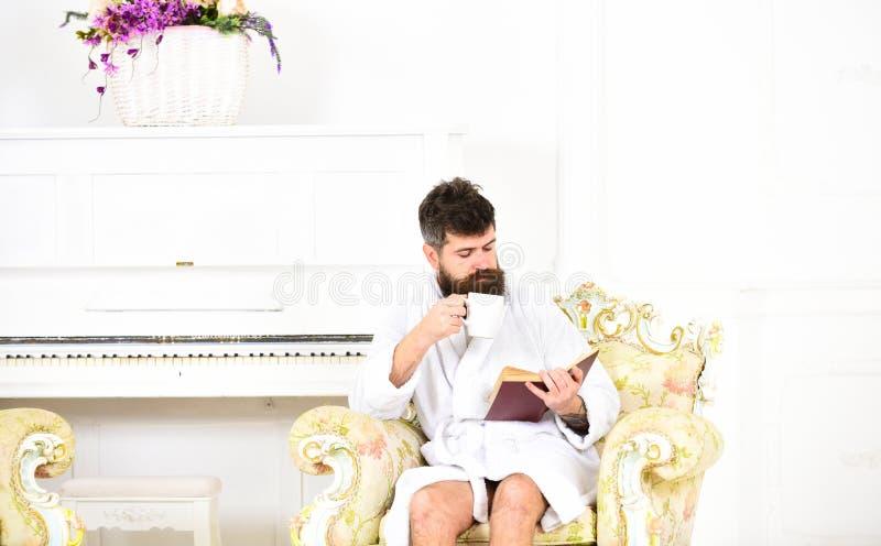 Укомплектуйте личным составом книгу чтения пока выпивающ кофе или чай Богатый парень сидя в античном кресле Наслаждаться совершен стоковые фотографии rf