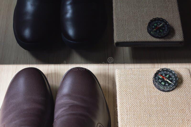 Укомплектуйте личным составом коричневые кожаные ботинки с блокнотом или дневником с компасом стоковые изображения