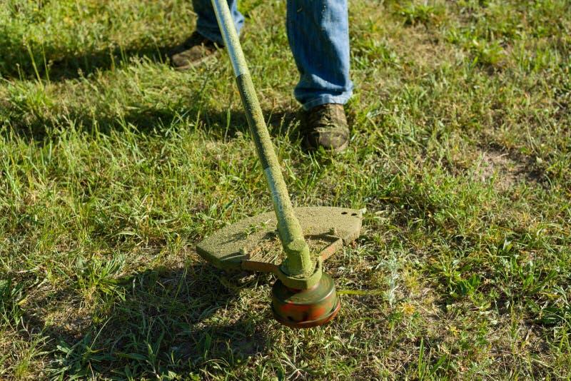 Укомплектуйте личным составом кося траву на сельской лужайке, конец-вверх стоковые изображения