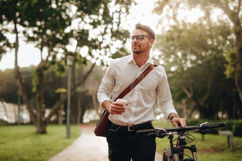 Укомплектуйте личным составом наслаждаться кофе и музыкой пока идущ к офису стоковое изображение rf