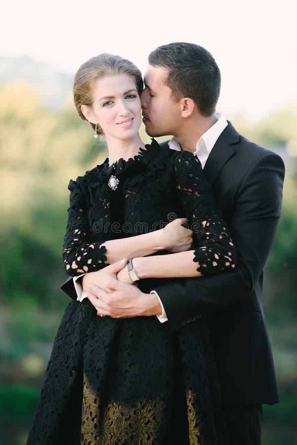 Укомплектуйте личным составом носить черный костюм обнимая и целуя стоковое изображение