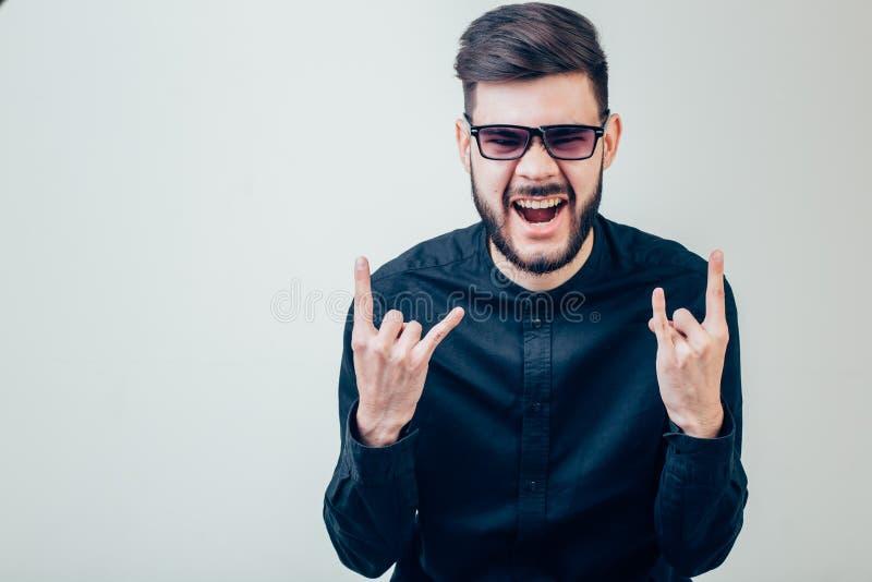 Укомплектуйте личным составом нося стекла показывая рожкам руки жеста рукой и и счастливое кричащее стоковые изображения rf