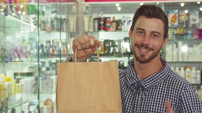 Укомплектуйте личным составом показывать пакет с товарами в аптеке стоковое изображение