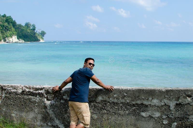 Укомплектуйте личным составом положение на пляже и смотреть море стоковые изображения rf
