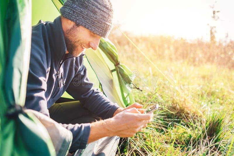 Укомплектуйте личным составом портрет путешественника используя его мобильный телефон и сидеть в лагере стоковые изображения rf