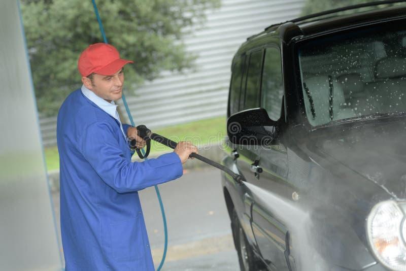 Укомплектуйте личным составом работу с высокой шайбой давления для того чтобы очистить автомобиль стоковые изображения rf
