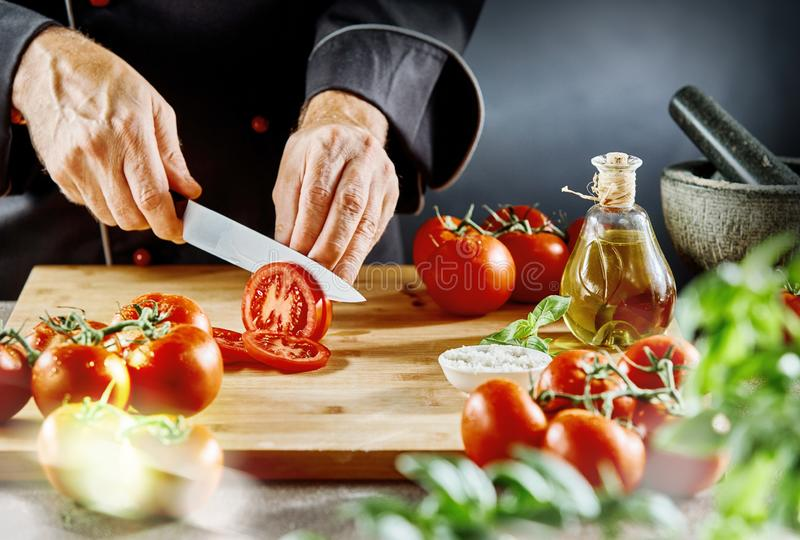 Укомплектуйте личным составом резать зрелые томаты в тонкие куски стоковые фото