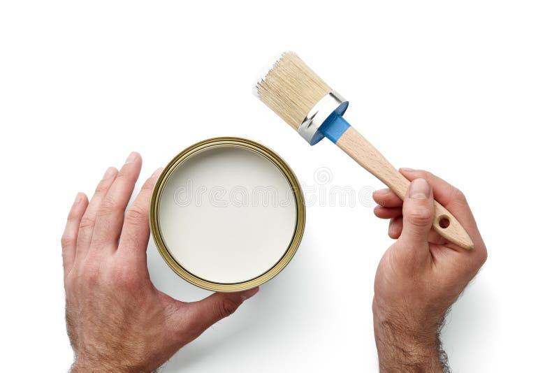 Укомплектуйте личным составом руки ` s держа кисть и смогите изолированный на белизне стоковое изображение