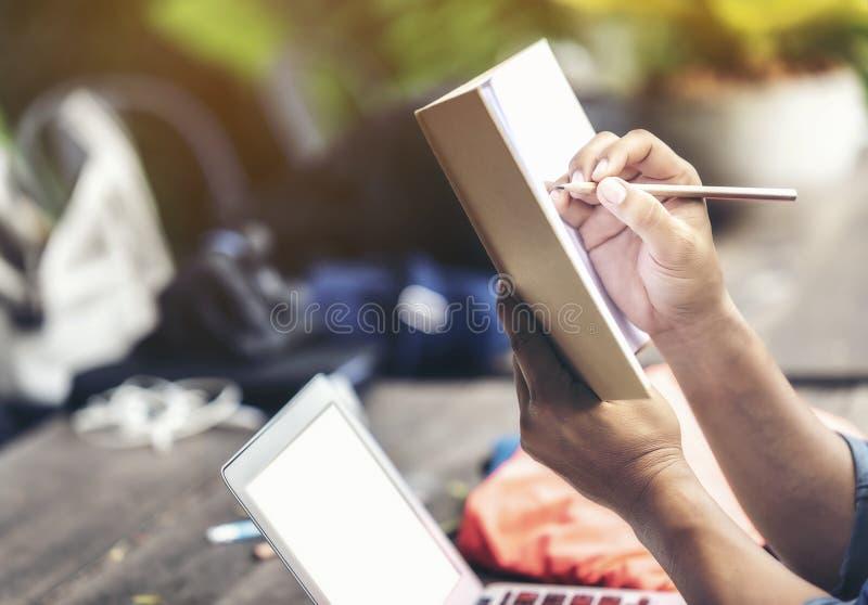 Укомплектуйте личным составом руку держа карандаш и тетрадь для того чтобы думать дизайна стоковая фотография