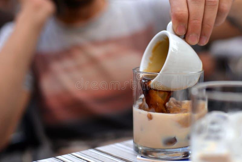 Укомплектуйте личным составом руку лить кофе в стекло с кубами льда стоковое изображение rf