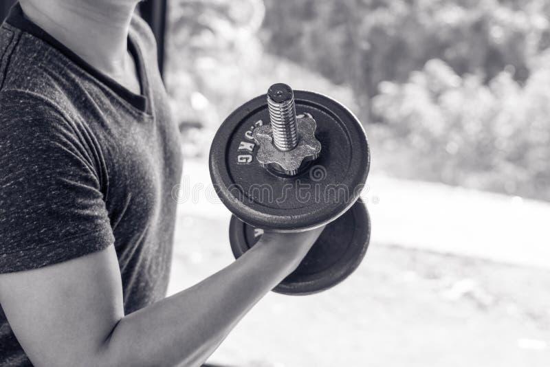 Укомплектуйте личным составом руку поднимая стальную гантель в изображении спортзала мышц остроени черно-белых, жизни и концепции стоковое фото