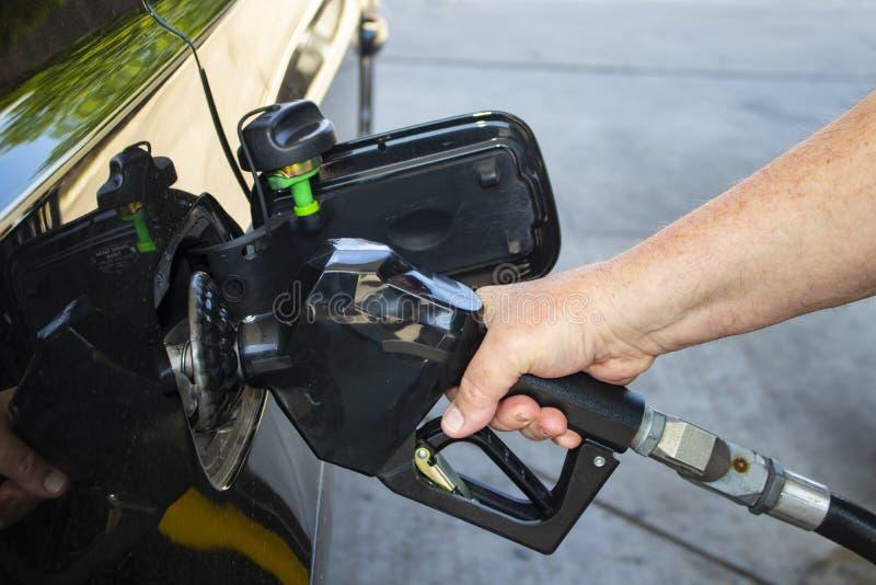 Укомплектуйте личным составом руку ` s держа сопло газового насоса и кладя газ в черный автомобиль стоковые фото