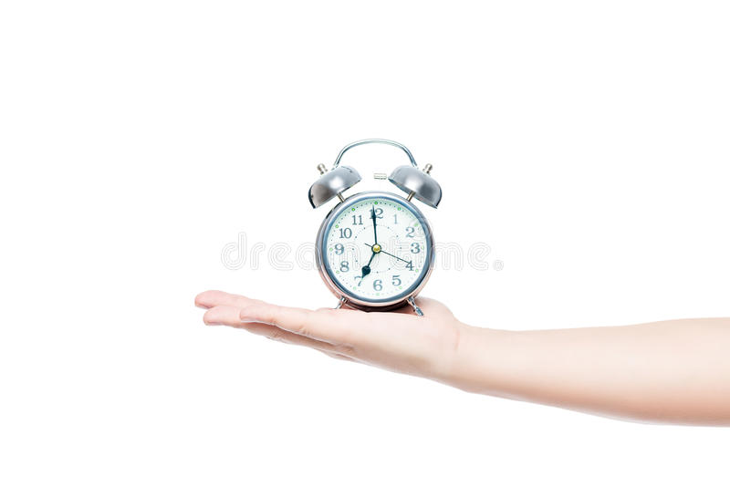 Укомплектуйте личным составом руку ` s на белой предпосылке изолированной с будильником внутри стоковое изображение rf