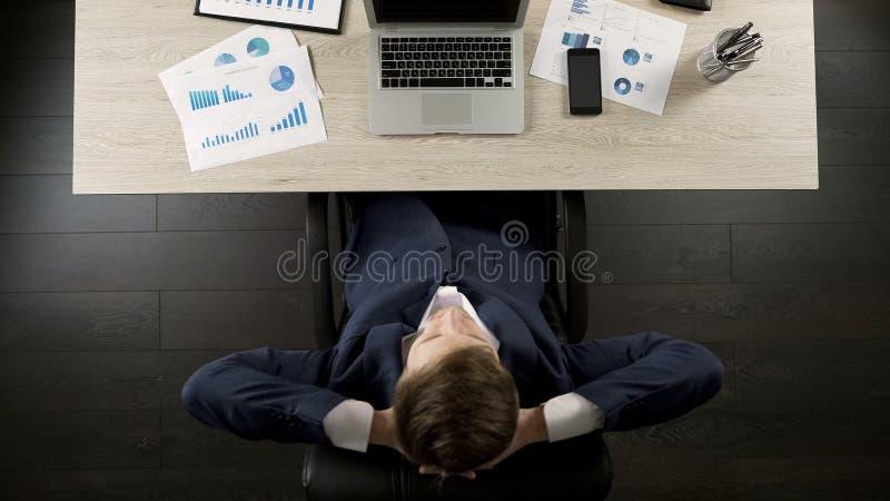 Укомплектуйте личным составом сидеть назад в стуле офиса ослабленном и, который удовлетворенном с проектом дела стоковое изображение
