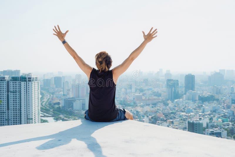 Укомплектуйте личным составом сидеть на черной крыше и покажите руку вверх с backgro голубого неба стоковое изображение