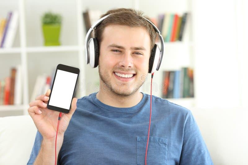 Укомплектуйте личным составом слушая музыку показывая пустой умный экран телефона стоковые фотографии rf