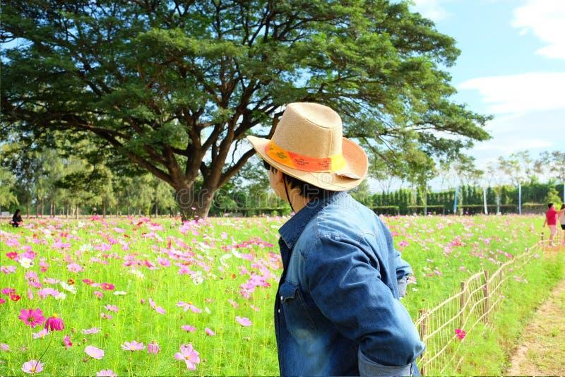 Укомплектуйте личным составом соломенную шляпу ` s заднюю нося пока смотрящ цветочный сад стоковые фото