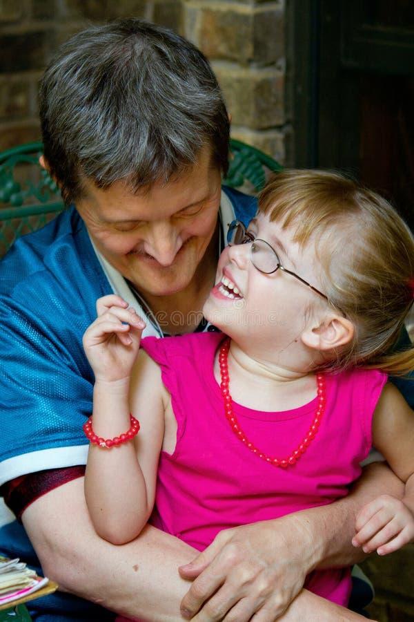 Укомплектуйте личным составом с владениями синдрома спусков его молодую племянницу по мере того как она смеется над стоковые фото