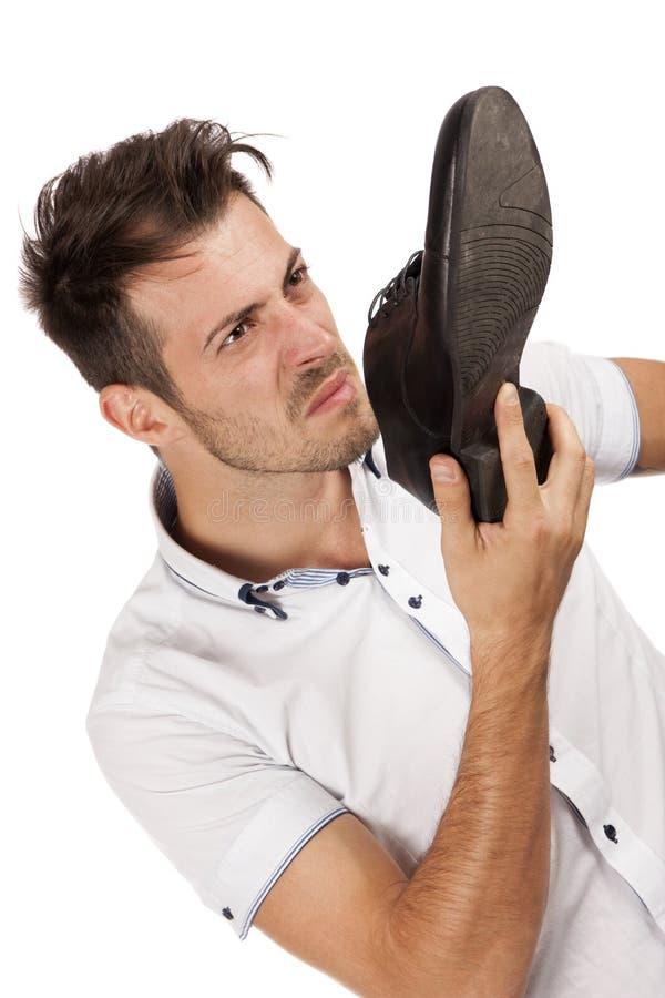 Укомплектуйте личным составом удерживание одно его ботинок близко к его носу стоковые фотографии rf