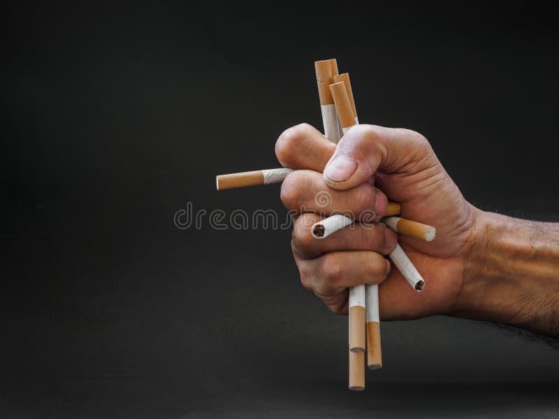 Укомплектуйте личным составом удерживание руки и разрушьте сигареты на черной предпосылке Qui стоковые изображения