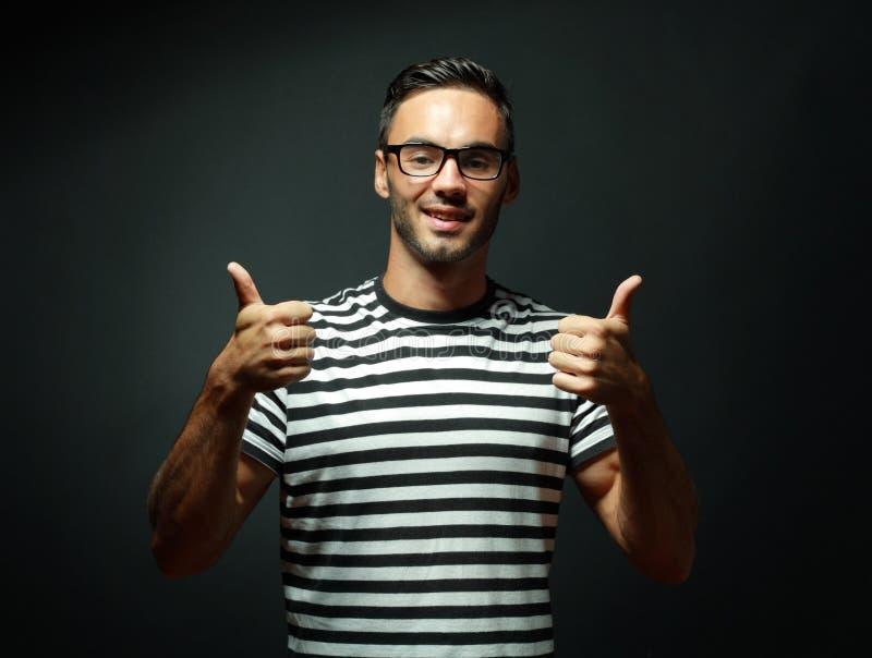 Укомплектуйте личным составом усмехаться и давать вам 2 большого пальца руки вверх стоковая фотография