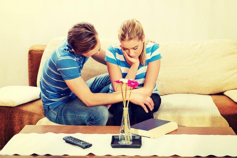Укомплектуйте личным составом утешать его партнера осадки в живущей комнате стоковые фотографии rf