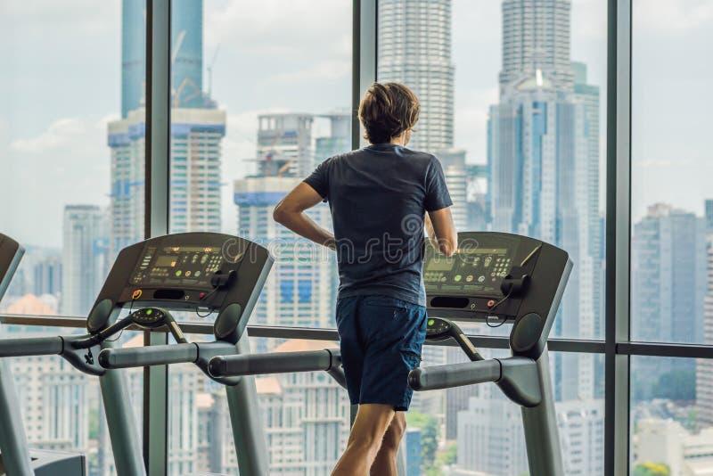 Укомплектуйте личным составом ход в спортзале на третбане на фоне большого города концепция для работать, фитнеса и здорового стоковое изображение