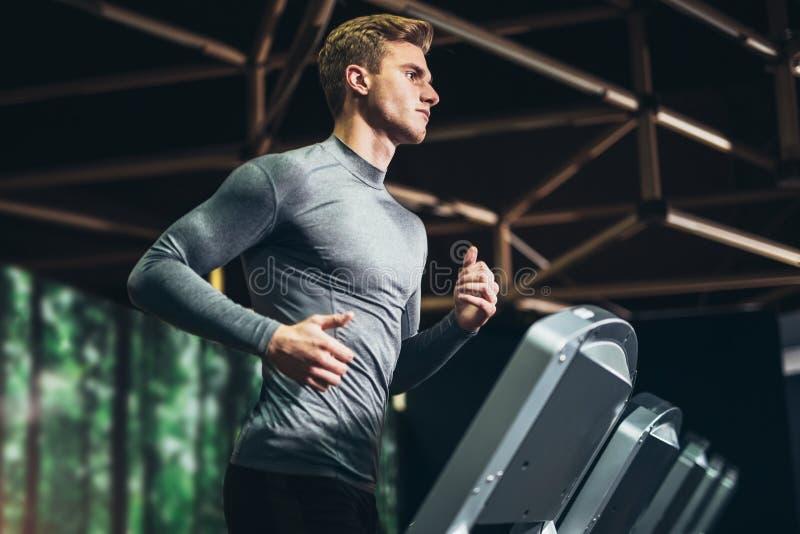 Укомплектуйте личным составом ход в спортзале на третбане стоковое фото rf