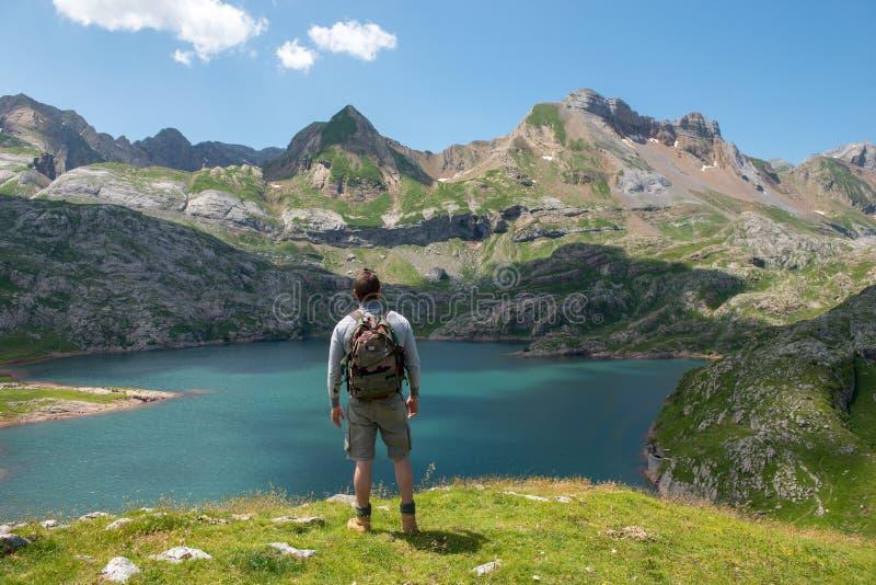 Укомплектуйте личным составом hiker отдыхая и смотря озеро в горах Пиренеи стоковые изображения
