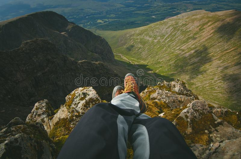 Укомплектуйте личным составом hiker сидя на верхней части утесов горы Красивая погода с природой Шотландии Деталь пеших ботинок н стоковые фотографии rf
