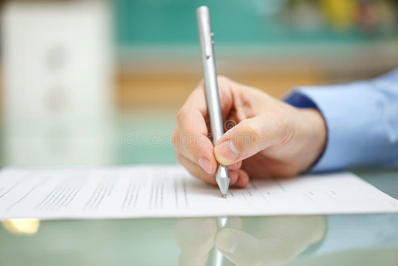 Укомплектовывает личным составом руку пишет документ дома на столе стоковое изображение